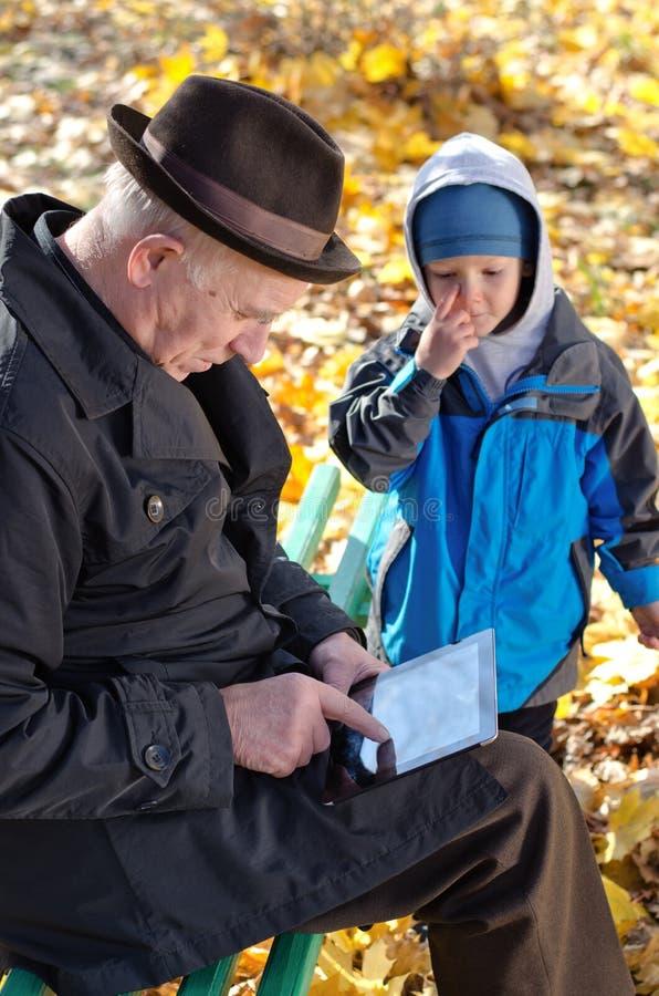 Avô que usa uma tabuleta olhada por seu neto foto de stock royalty free