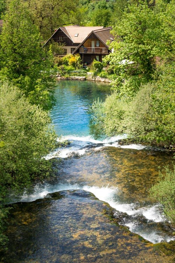 By av Rastoke vid en Korana flod med trähus och en vattenfall, Kroatien arkivbilder