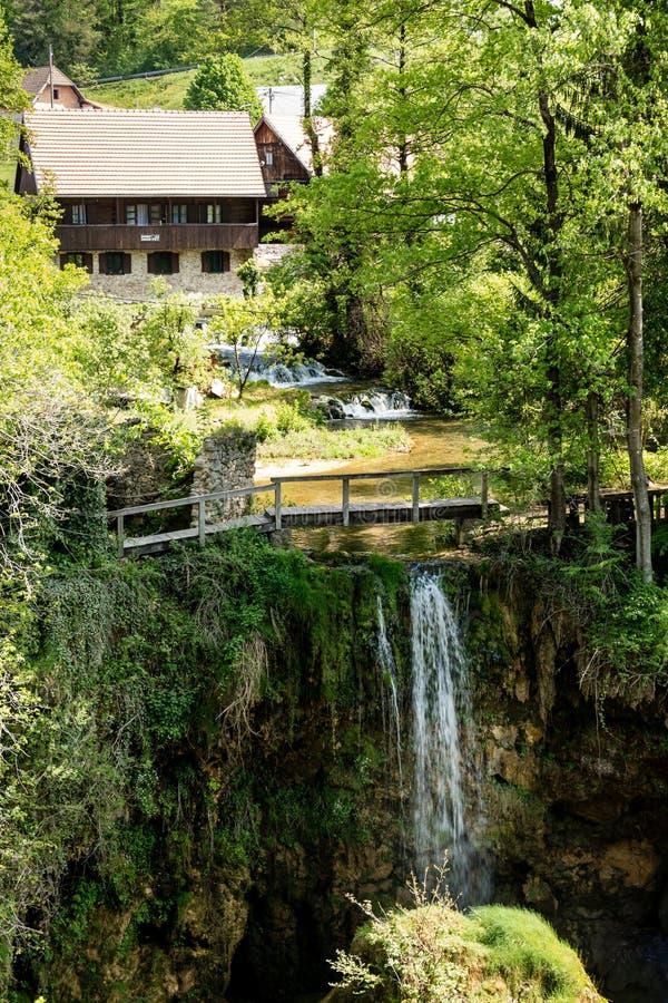 By av Rastoke vid en Korana flod med trähus och en vattenfall, Kroatien royaltyfri bild
