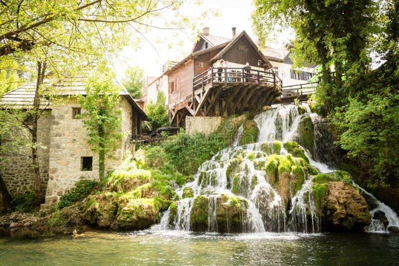 By av Rastoke vid en Korana flod med trähus och en vattenfall, Kroatien royaltyfri fotografi