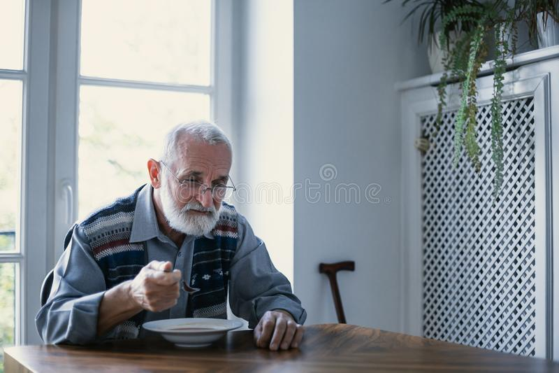 Av? superior com cabelo cinzento e barba que senta-se apenas na cozinha que comem o caf? da manh? fotos de stock royalty free