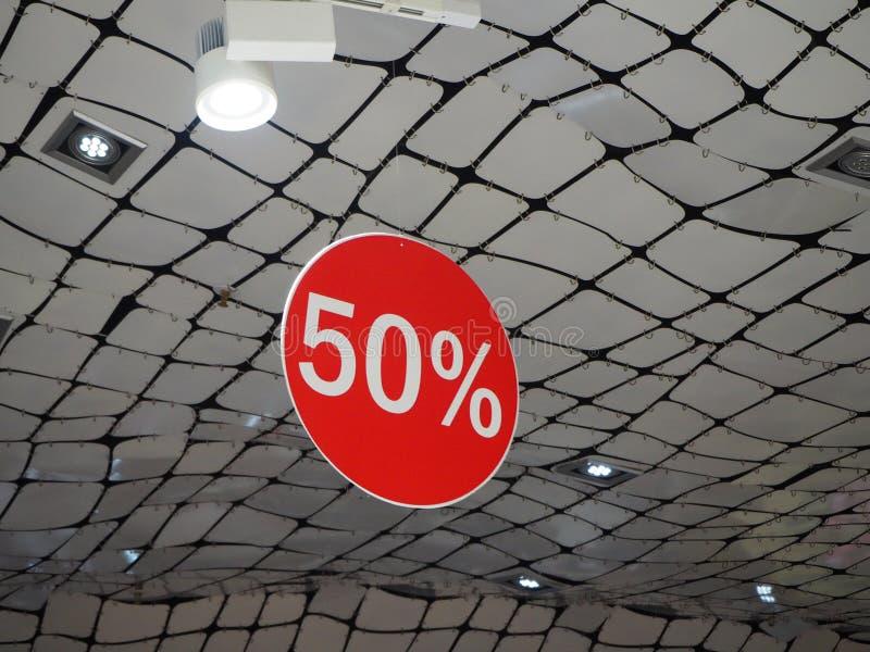 50% av tecknet för försäljning för prisrabattbefordran som det röda hänger från taket i lagret fotografering för bildbyråer