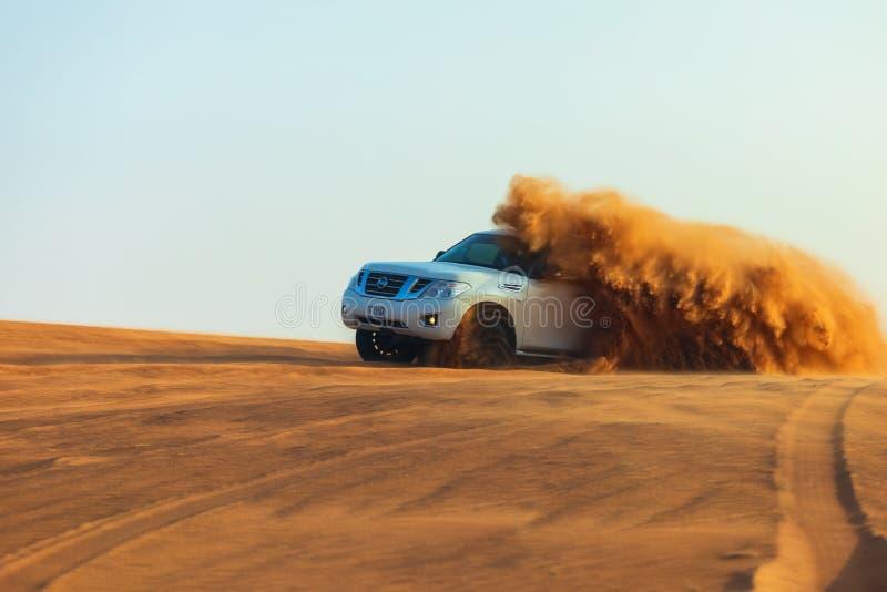 Av-väg affärsföretag med SUV i arabisk öken på solnedgången Offroad medel som slår till och med sanddyn i den Dubai öknen royaltyfri bild