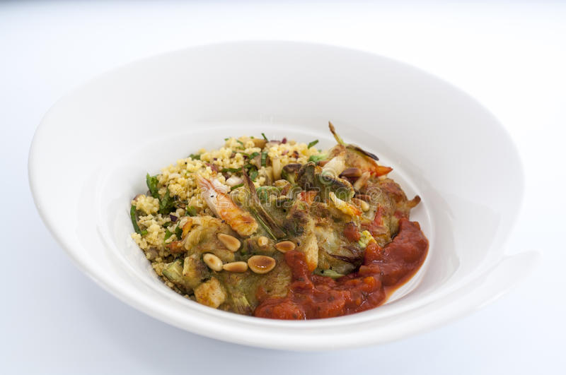 Avacado and cous cous with tomato relish. And pine nuts royalty free stock photos