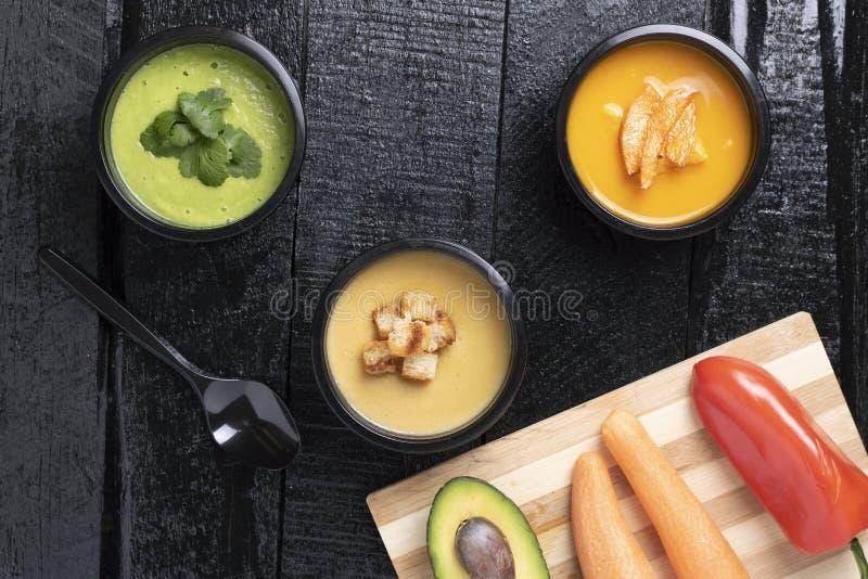 Avacado hecho en casa, calabaza, sopa de guisantes, zanahoria y pimienta en el tablero de la cocina, lugar para el texto, comida  fotos de archivo libres de regalías