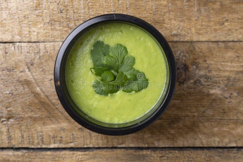 Avacado soppa och mintkaramell i matbeh?llare med skeden, klart m?l som ska ?tas royaltyfri fotografi