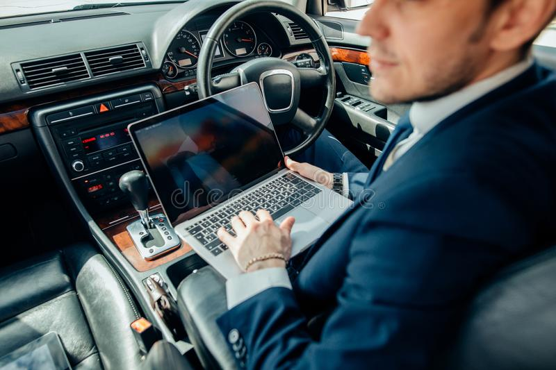 Focusing on work. businessman working on laptop while sitting on back seat car stock images