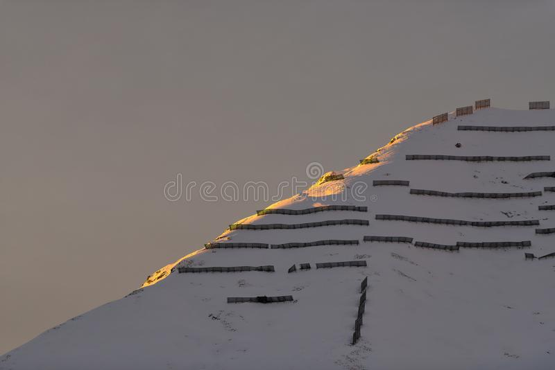 Avalanche barriers in the mountains at sunset.  stock photo