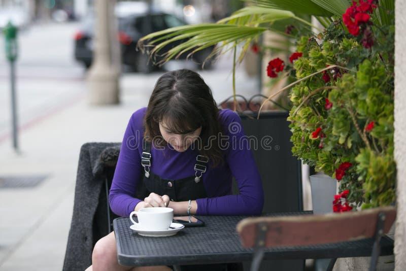 Avaliação da mulher ou revisão de uma cafetaria ou de um restaurante em linha com telefone celular imagens de stock