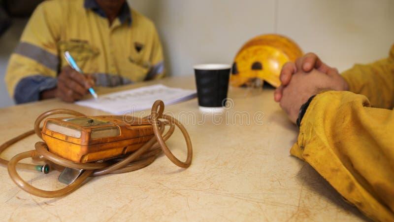 Avaliação de risco escrita da análise de perigo JHA do trabalho do trabalhador da construção mão asiática na tabela imagem de stock