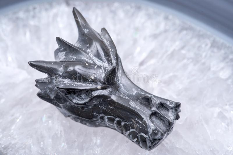Avalon dragon skull on polished large natural agate slab from Brazil. Healing Crystal. Avalon dragon skull on polished large natural agate slab from Brazil stock photography