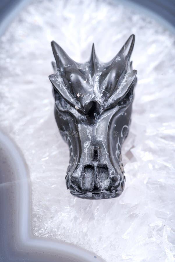 Avalon dragon skull on polished large natural agate slab from Brazil. Healing Crystal. Avalon dragon skull on polished large natural agate slab from Brazil royalty free stock photo