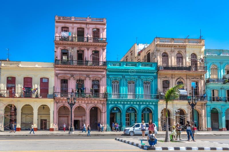 Avana, Cuba - 11 marzo 2018 - una via variopinta in pieno delle case, stile coloniale, cielo blu, turisti che prendono le immagin immagine stock libera da diritti