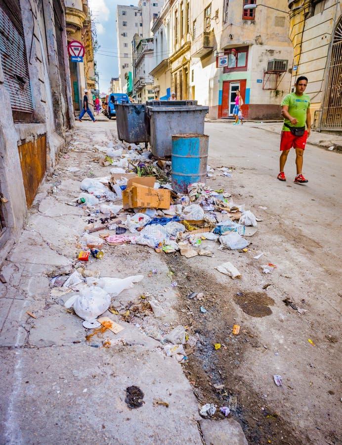 AVANA, CUBA - 28 ottobre - uomo cammina dai mucchi di rifiuti e di immondizia nelle vie di Avana, Cuba il 28 ottobre 2015 fotografia stock libera da diritti