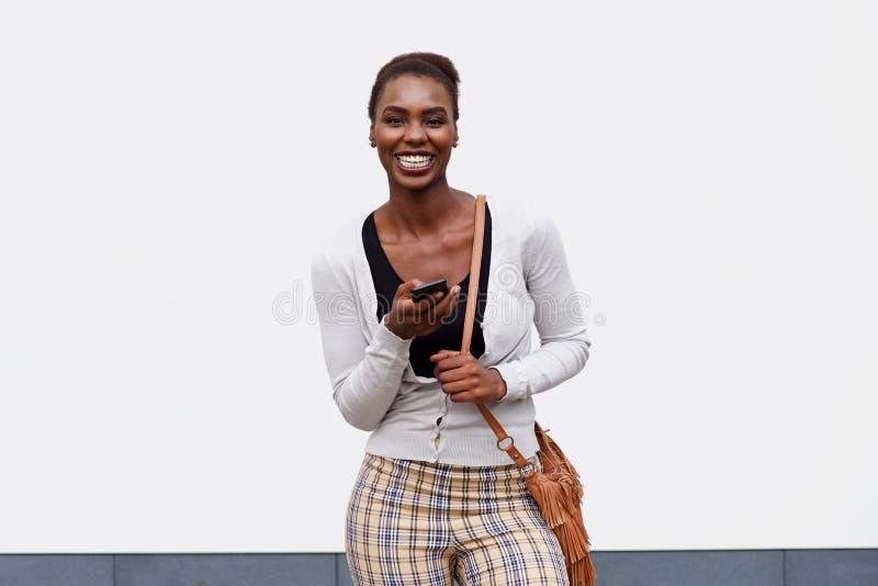 Avant de jeune femme de couleur souriant avec le téléphone portable et le sac à main photo libre de droits