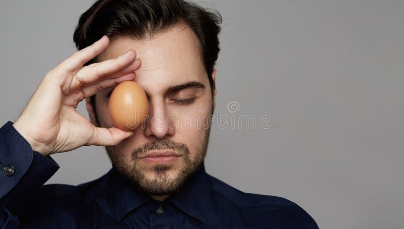 Avant organique frais d'oeufs d'homme de poulet sûr de participation de VISAGE SUR LE FOND GRIS Fin vers le haut photographie stock