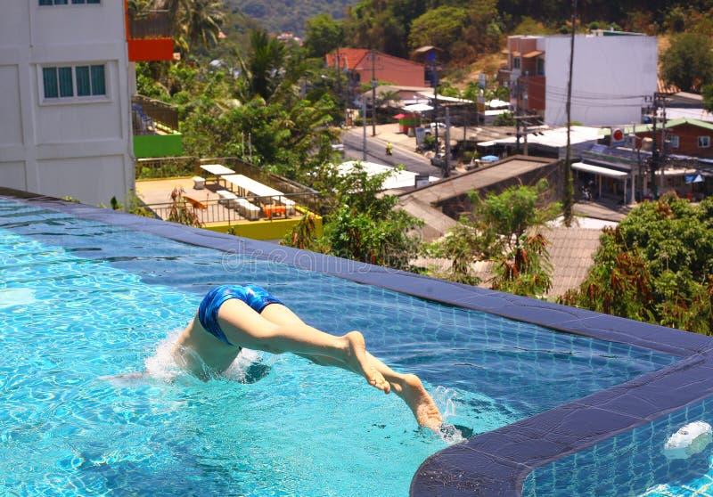 Avant principal sautant de garçon dans la piscine photographie stock libre de droits