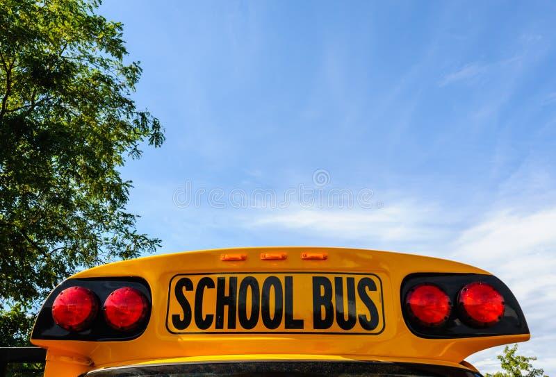 Avant supérieur d'autobus scolaire sur le ciel près des arbres photos libres de droits