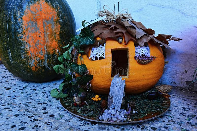 Avantgarde halloween carved pumpkin jack o lantern as house in woods, possibly witch house royalty free stock photography