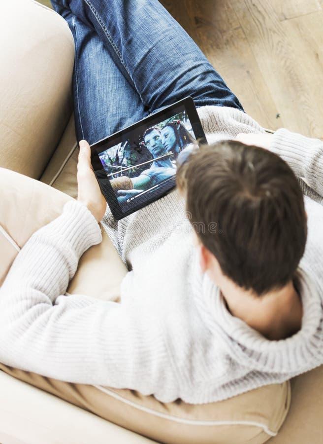 Avatar de observação do filme do homem no iPad imagem de stock