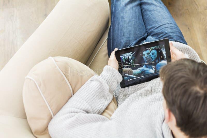 Avatar de observação do filme do homem no iPad imagens de stock