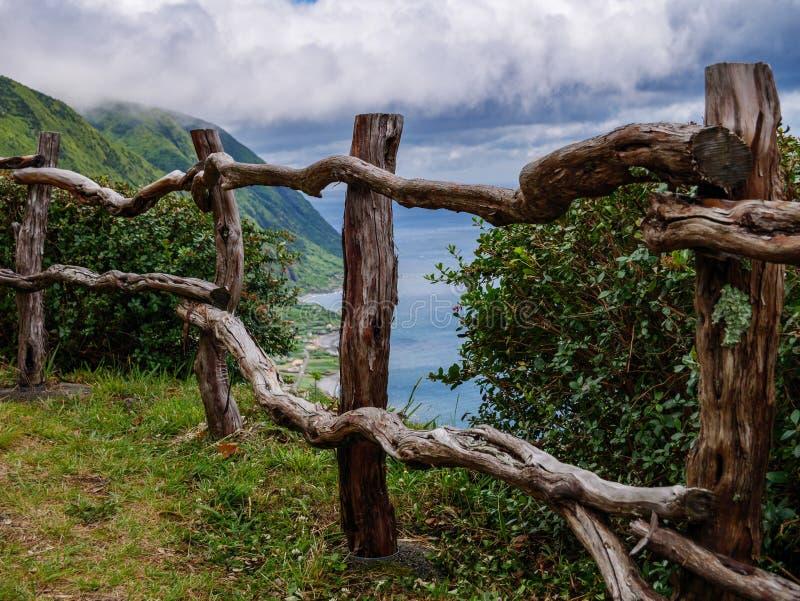 Avbilda av wodden staketet framme av en klippa med kusten och havet i bakgrunden royaltyfri fotografi