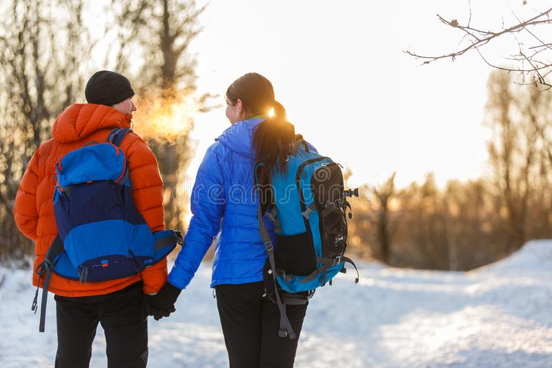 Avbilda från baksida av mannen och kvinnan med ryggsäckar i vinterskog arkivfoto
