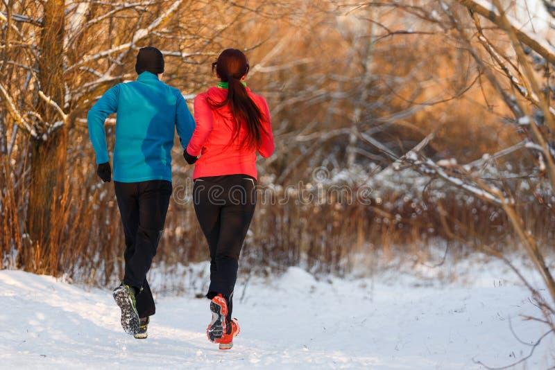 Avbilda från baksida av sportar kvinna och manspring på vinter fotografering för bildbyråer