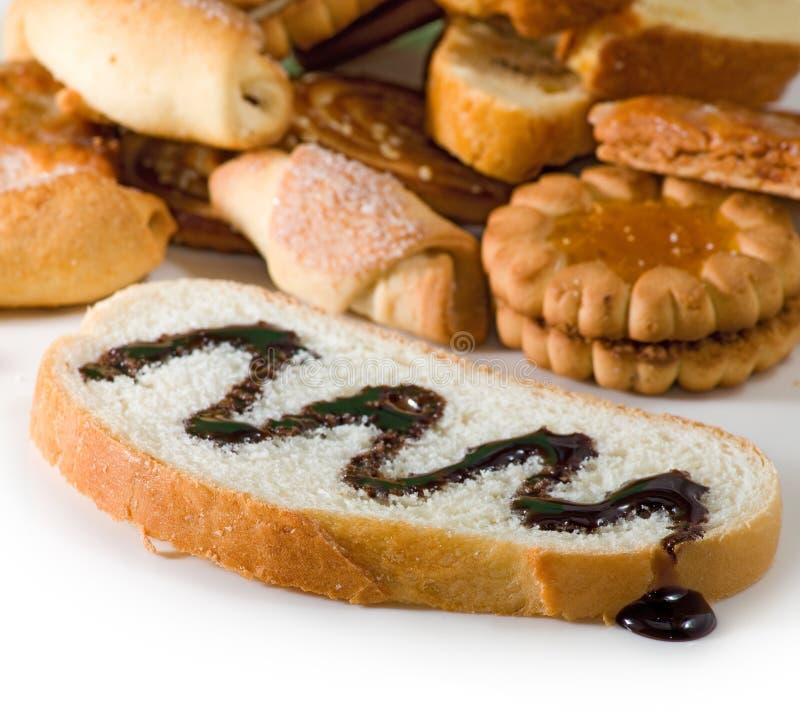Avbilda skivan av vitt bröd som bevattnas med vätskechoklad och kakor arkivbilder