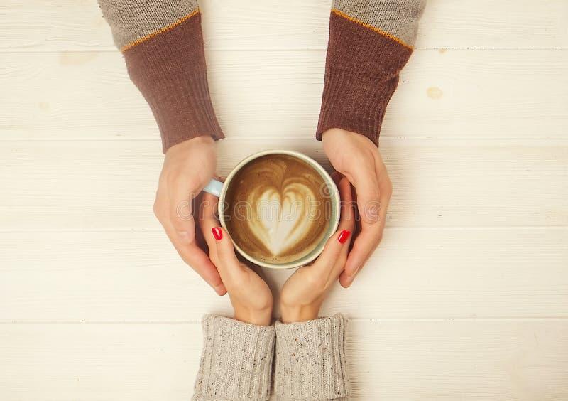 Avbildar förälskade innehavhänder för par med koppen av den bästa sikten för coffe på vit träbakgrund Mannen rymmer handen för kv royaltyfria foton