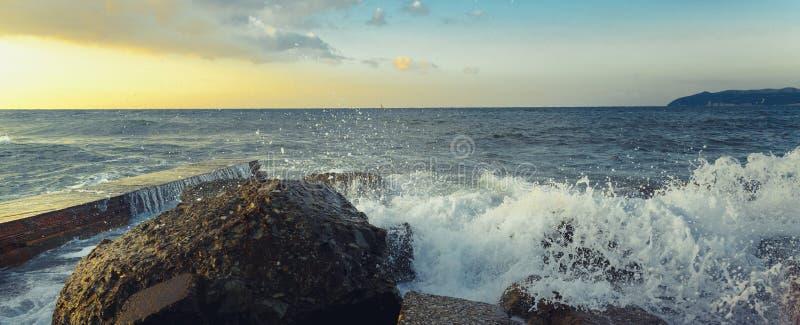 Avbrott för havsskumvågor på de kust- stenarna på horisontbakgrund arkivbilder