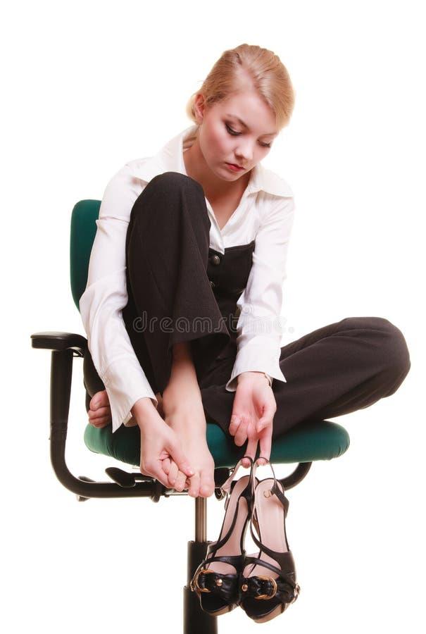 Avbrott från arbete Den trötta affärskvinnan med benet smärtar arkivfoto