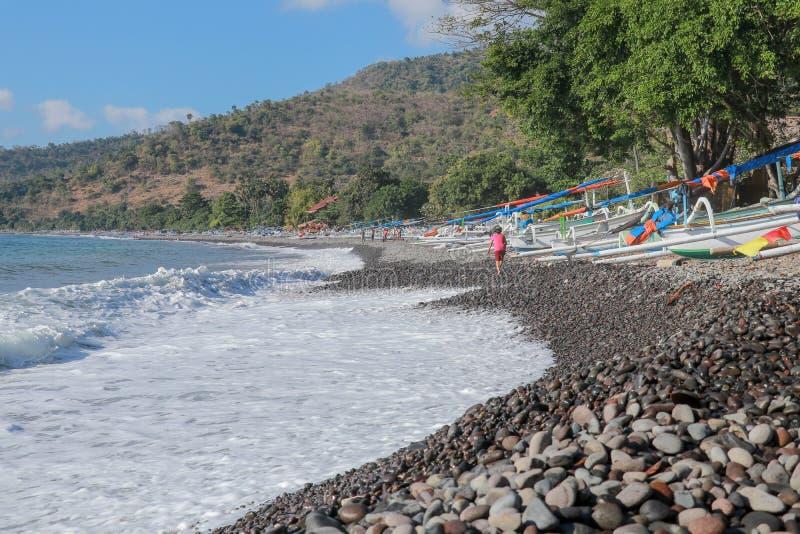 Avbrottet för havskusten anfaller en stenig strand i Bali, Indonesien Havsskum rullar över ett Pebble Beach Havet visar av dess m arkivbild