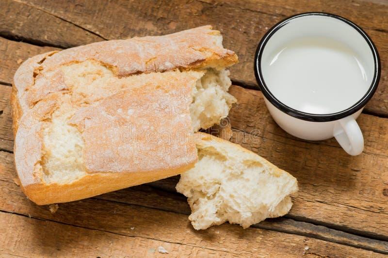 Avbrottet släntrar av ciabattabröd med mjölkar arkivbild