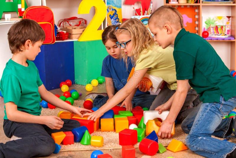 Avbrottsskolan av barn som spelar i ungar, skära i tärningar inomhus royaltyfria foton