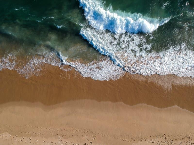 Avbrottsvågor och sandigt vatten arkivbilder