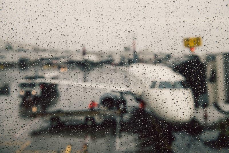 Avbrutet flyg under begrepp för vädervillkor Flygplan på porten under massivt regn Fördröjningflyg arkivfoto