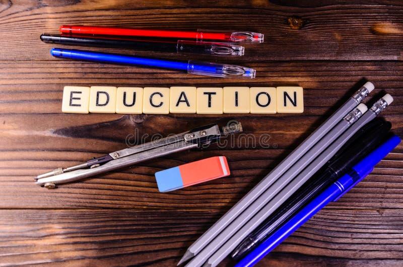 Avdelare, blyertspennor och radergummi på trätabellen Utbildningsinscripti royaltyfri foto