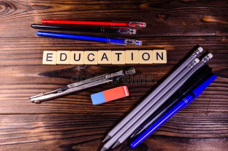 Avdelare, blyertspennor och radergummi på trätabellen Utbildningsinscripti royaltyfri fotografi