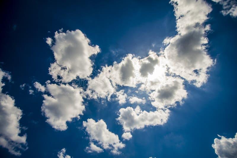 Avec des nuages cachant le soleil contre un ciel bleu profond image libre de droits