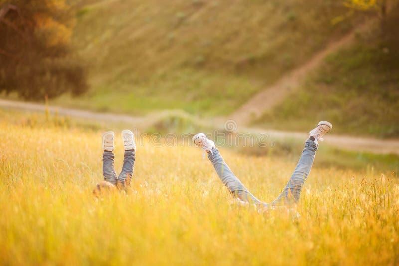 Avec l'arrivée des enfants, le monde est tourné à l'envers, les pieds d'enfants regardent hors de l'herbe photo stock