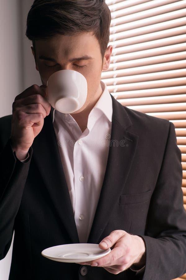 Avec la tasse tenant la fenêtre proche avec la jalousie photo libre de droits