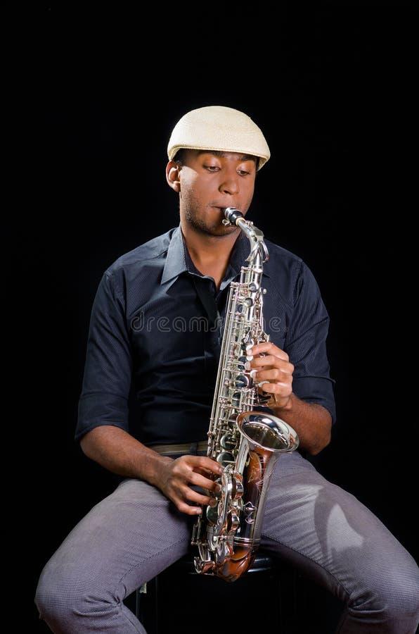 Avec le chapeau blanc un homme de couleur est reposant et jouant son saxophone, fond foncé, musique gentille photo stock