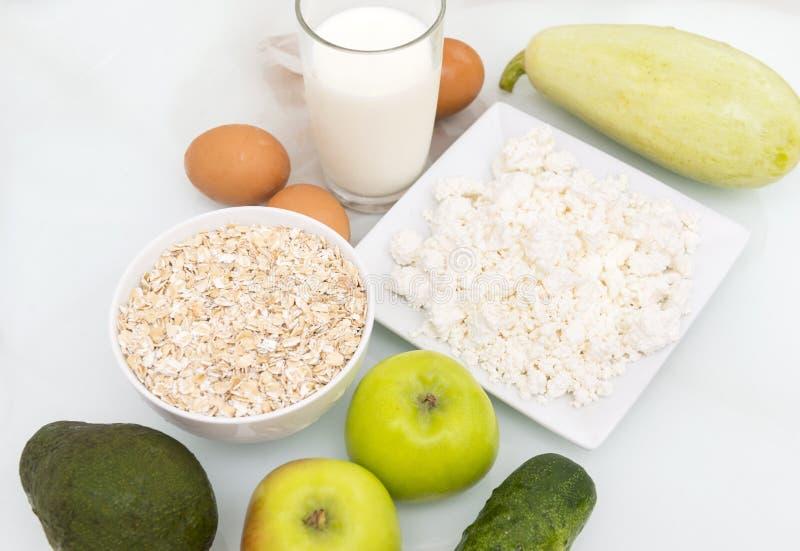 a aveia lasca-se, um vidro do leite, requeijão, ovos, maçãs, avoca foto de stock