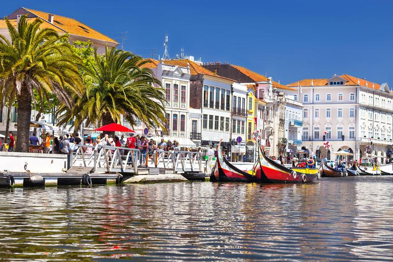 Aveiro, Portugal – May 3, 2019:  Moliceiro traditional colorful boats docked along the central canal with houses in Aveiro. royalty free stock photo