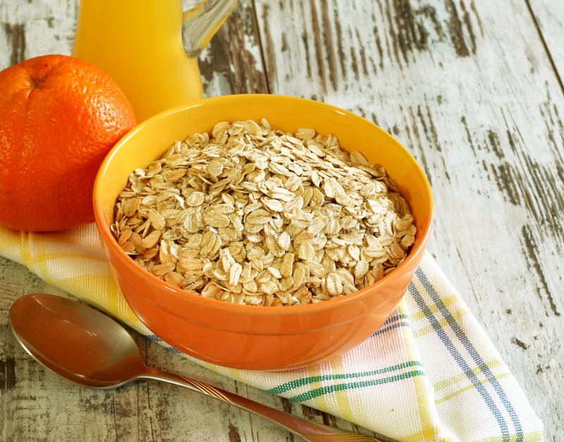 Avena en tazón de fuente, naranja fresca y jugo en de madera fotografía de archivo