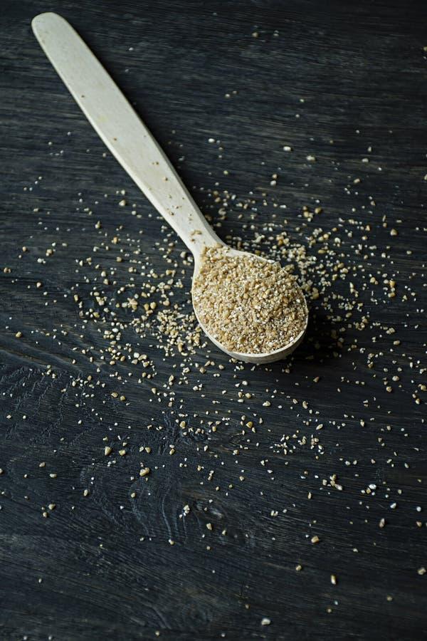 Avenas mondadas del trigo en una cuchara de madera en un fondo oscuro de madera Cuchara de madera con los granos del trigo imagenes de archivo