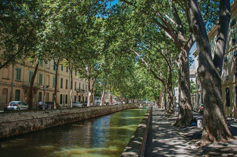 Avenida con la acera llena de árboles, canal al cielo azul de centro y soleado, en Nimes fotografía de archivo