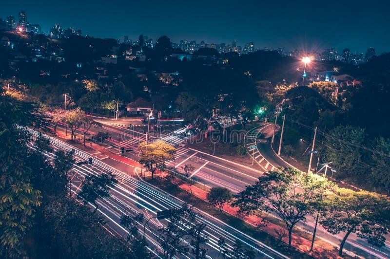 Avenida encendida por las luces de la ciudad imagenes de archivo