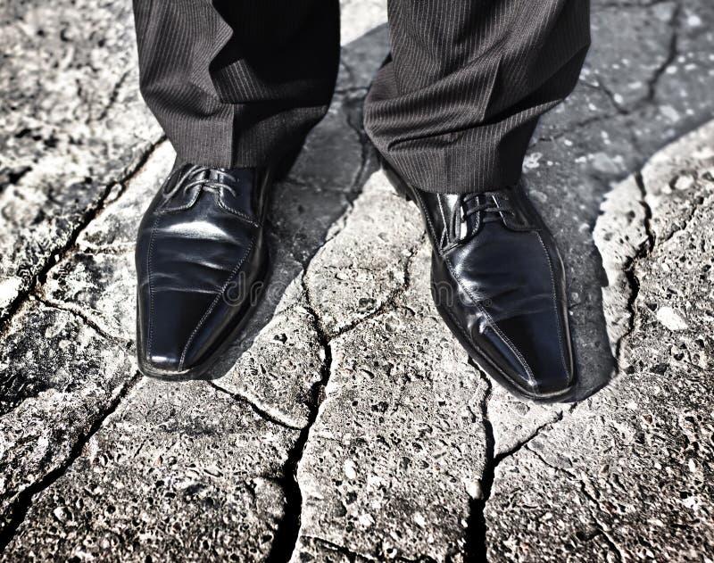 Jambes d'homme d'affaires se tenant sur une terre criquée photographie stock libre de droits